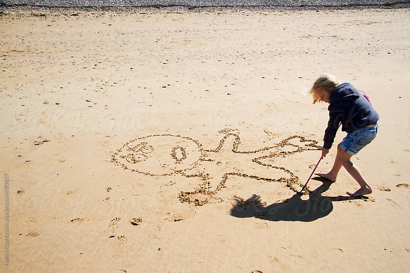 A little girl drawing in sand on a beach. by Helen Rushbrook for Stocksy United