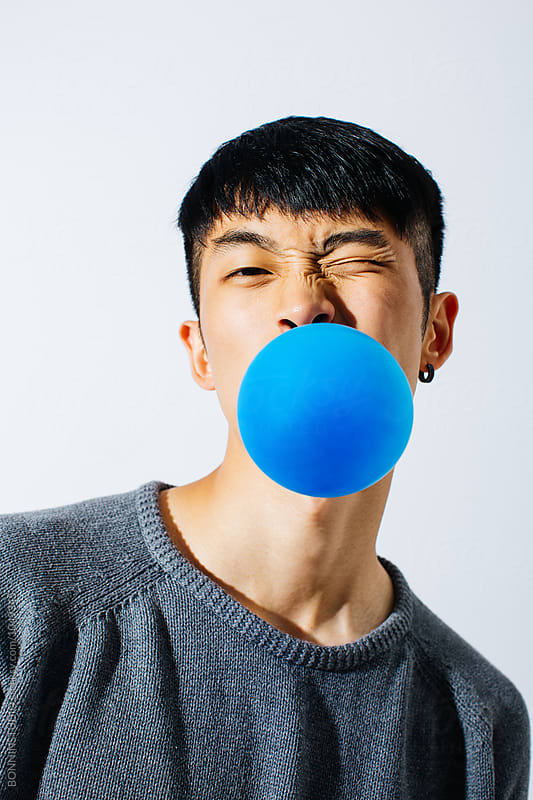 Asian man blowing a blue balloon over white background.  by BONNINSTUDIO for Stocksy United
