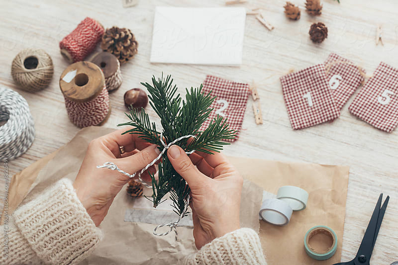DIY Christmas - Female Hands Tying Fir Twigs Together for Homemade Xmas Gift by VISUALSPECTRUM for Stocksy United