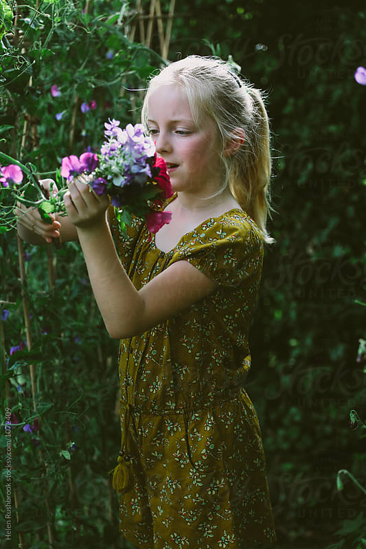 A little girl picking flowers in a garden. by Helen Rushbrook for Stocksy United