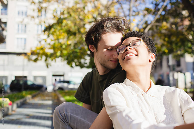 Young couple in love sitting outdoors by michela ravasio for Stocksy United
