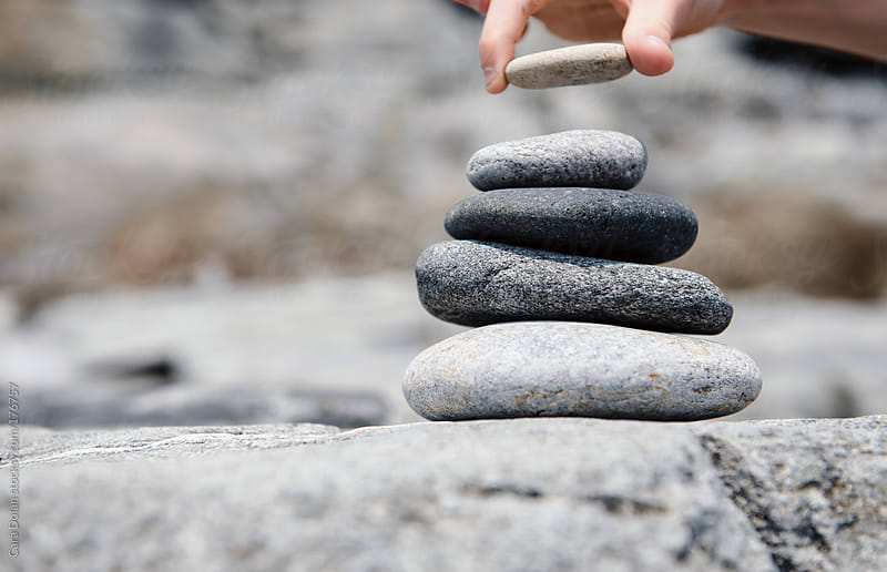 Hand placing a smooth beach stone on top of a stack by Cara Dolan for Stocksy United