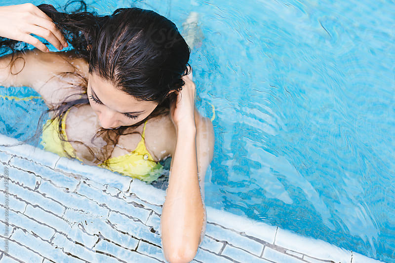 Young woman resting against the edge of the pool by michela ravasio for Stocksy United