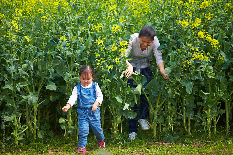 happy little girl having fun in the spring field with her mother by Bo Bo for Stocksy United