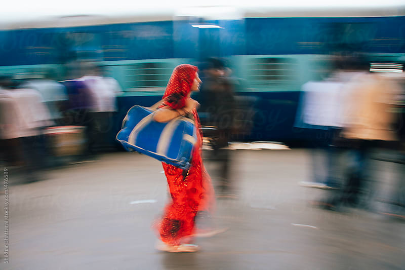 A woman in a hurry at a train station in India.  by Shikhar Bhattarai for Stocksy United