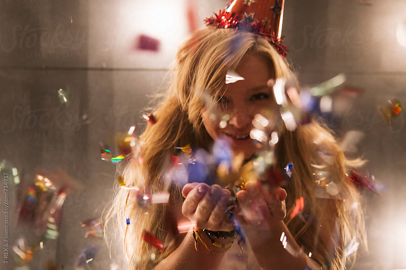 Girl blowing tinsel in the camera by Danil Nevsky for Stocksy United