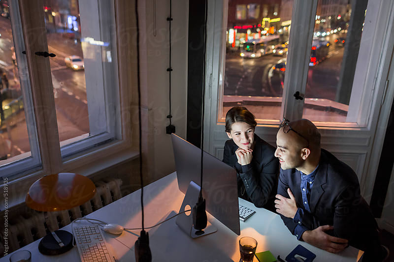 Two Business People Working Late by VegterFoto for Stocksy United