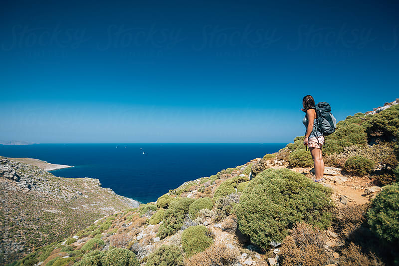 Female hiker with backpack on a trail overlooking an ocean view by Micky Wiswedel for Stocksy United