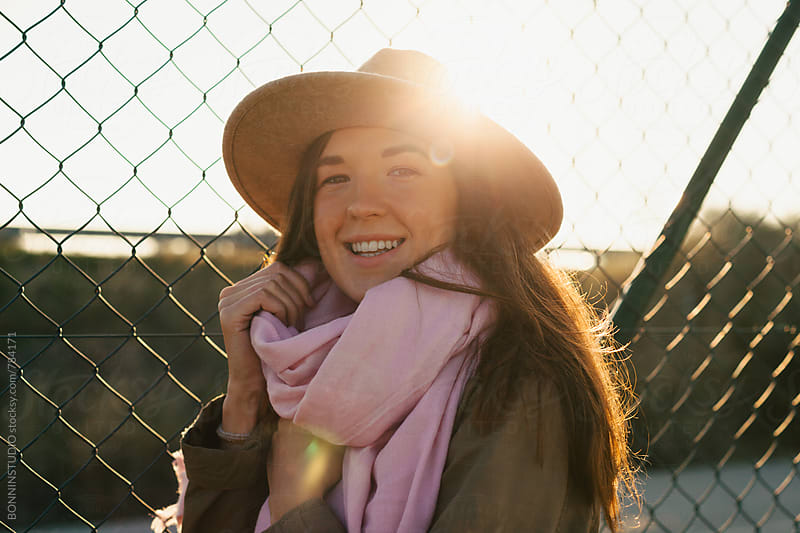 Portrait of a smiling woman standing by a fence at sunrise. by BONNINSTUDIO for Stocksy United