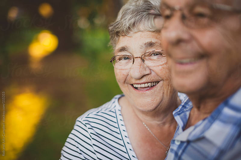 Cute elderly woman smiling with husband by Rob and Julia Campbell for Stocksy United