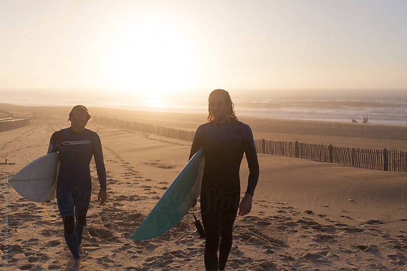 Two surfers walking back up the beach after a late afternoon surf session by Denni Van Huis for Stocksy United