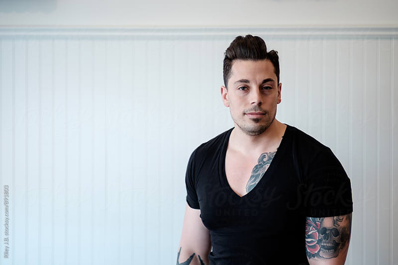 Tattooed man wearing a black deep V-neck shirt. by Riley Joseph for Stocksy United