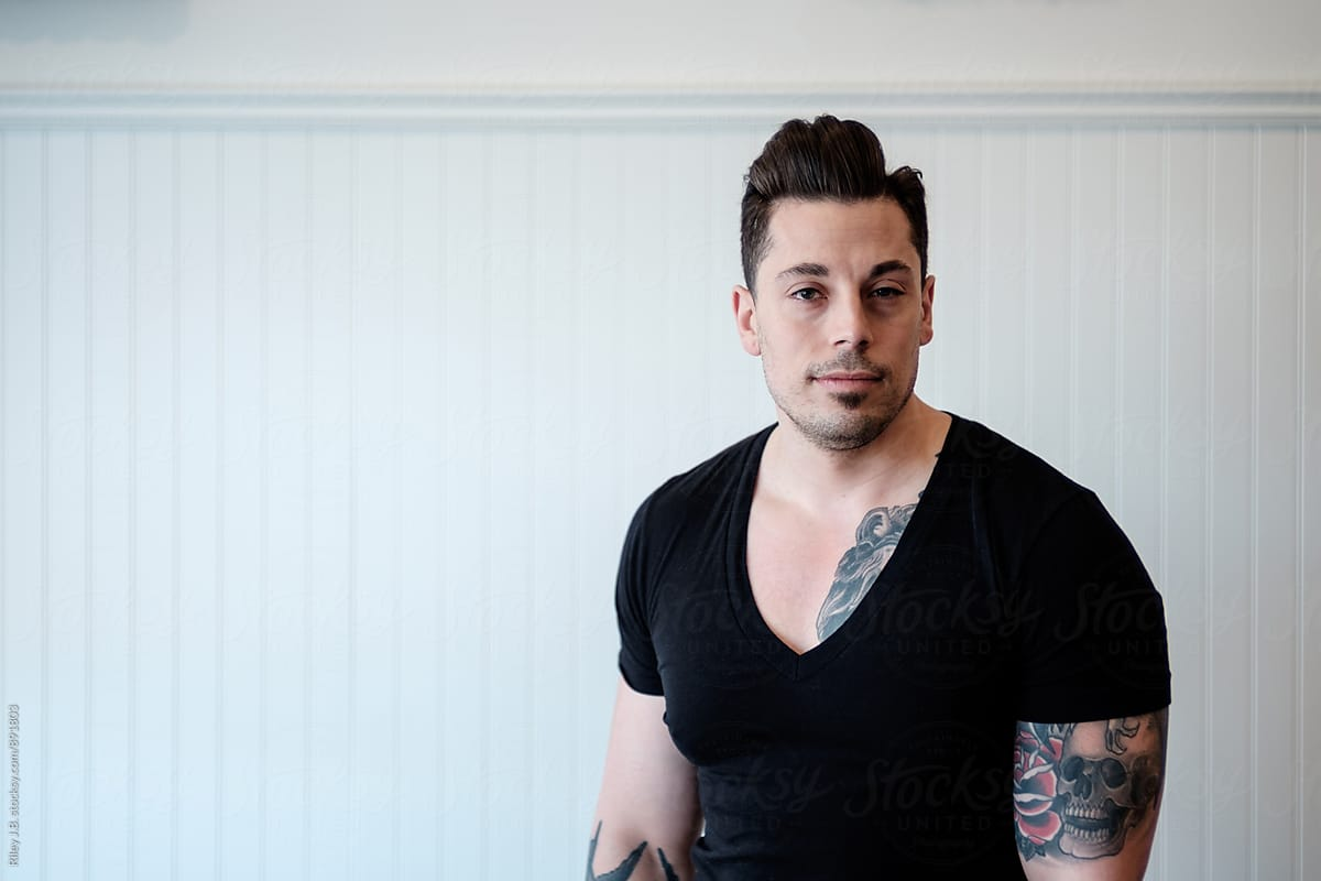Tattooed Man Wearing A Black Deep V Neck Shirt By Riley Jb
