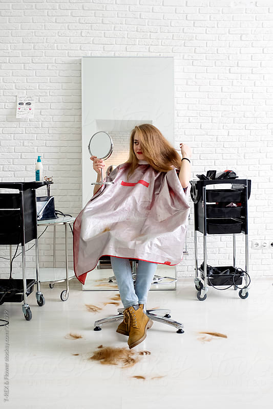 Client at barbershop looking at mirror on her hair by Danil Nevsky for Stocksy United