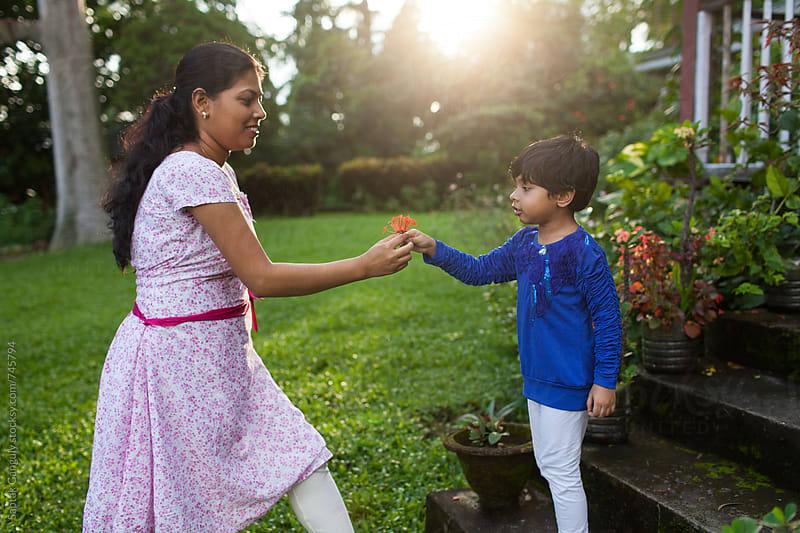 Little girl giving flower to her mother by Saptak Ganguly for Stocksy United