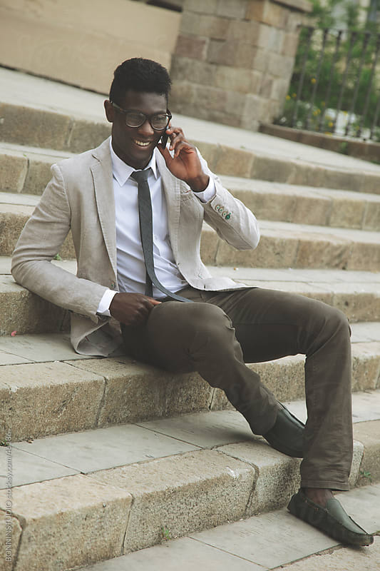 African young businessman sitting in stairs and talking on smartphone by BONNINSTUDIO for Stocksy United