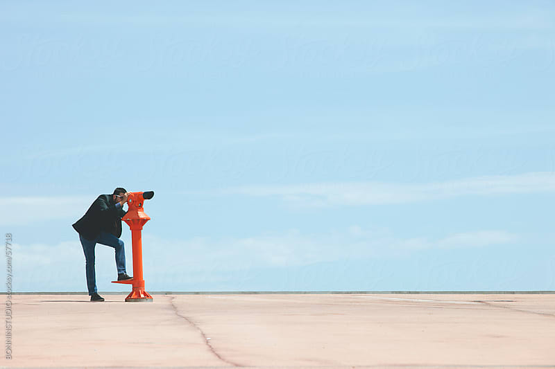 Young businessman looking with red telescope in front of blue sky. by BONNINSTUDIO for Stocksy United