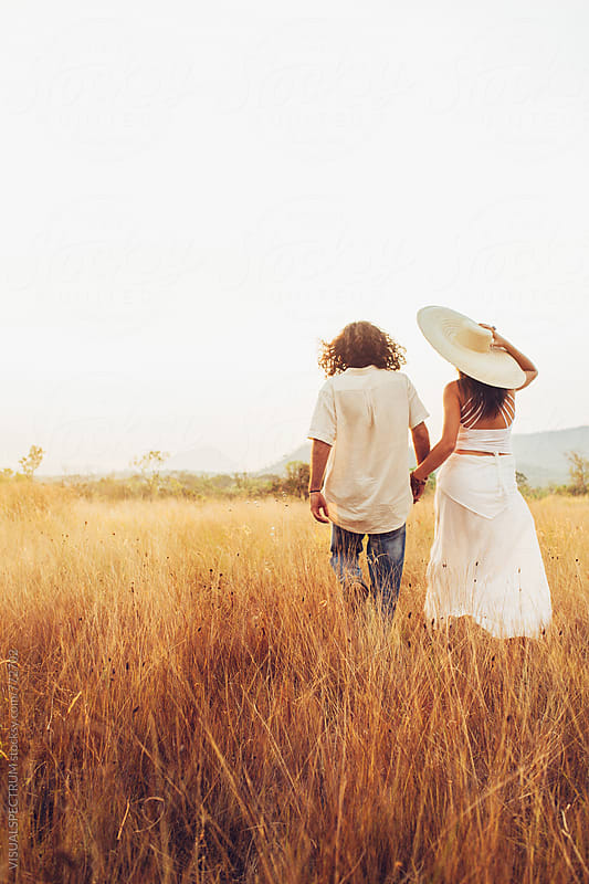 Romance - Good-Looking Young Couple Walking Together in Dry Grassland by VISUALSPECTRUM for Stocksy United
