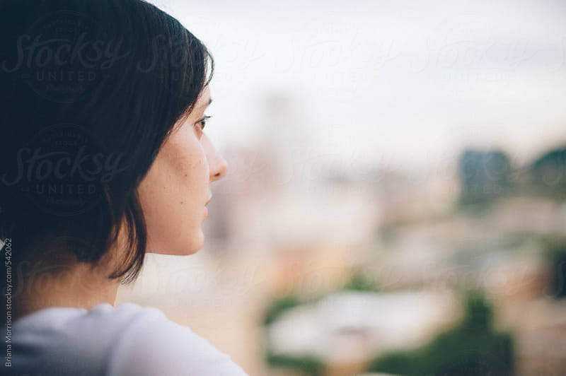 Profile of a Woman Gazing out on a City by Briana Morrison for Stocksy United