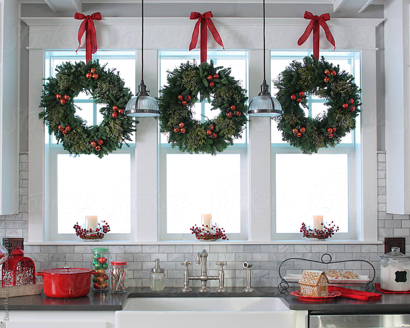 Festive kitchen windows with wreaths by Daniel Hurst for Stocksy United