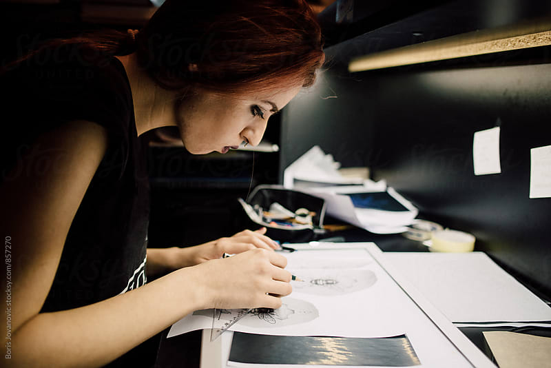 Female tattoo artist drawing a tattoo on paper by Boris Jovanovic for Stocksy United