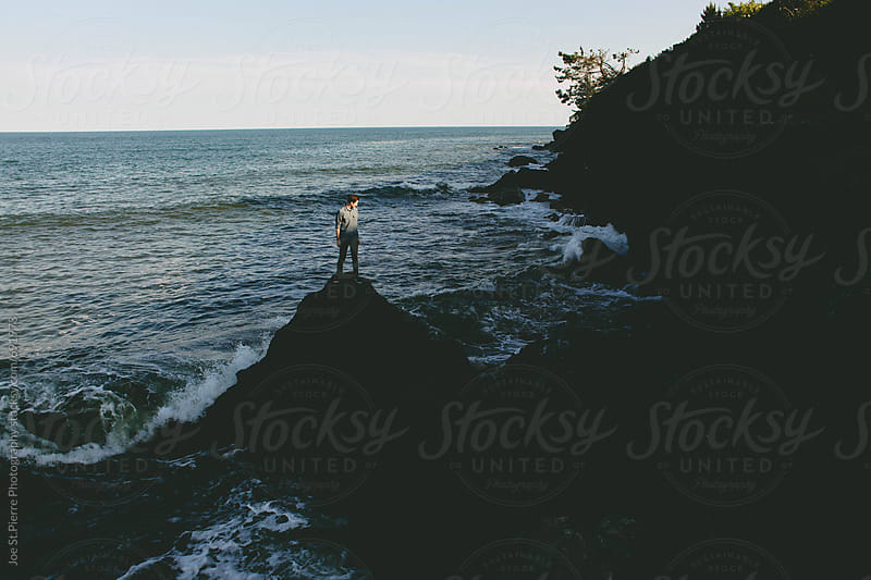 Young man standing by the ocean by Joe St.Pierre Photography for Stocksy United