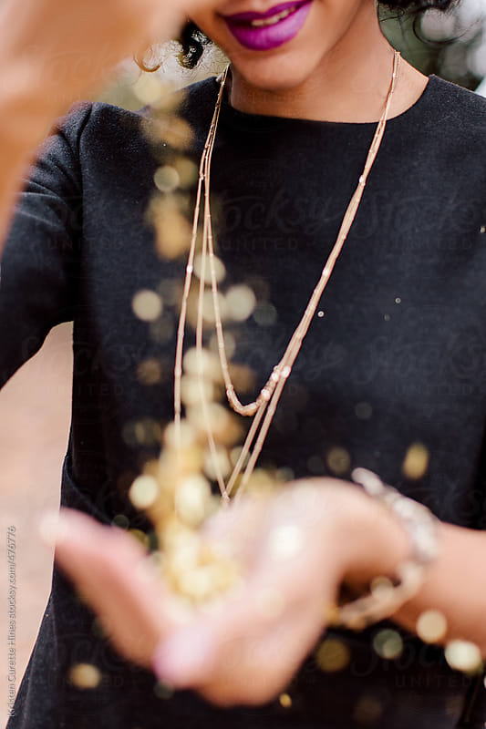 Woman pouring gold confetti / glitter in her hands by Kristen Curette Hines for Stocksy United