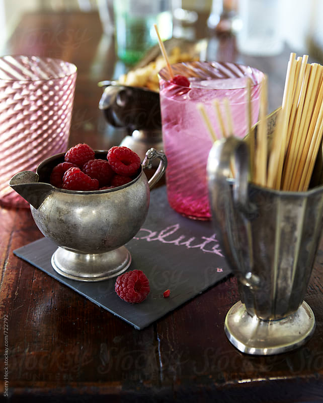 Home bar with raspberry fizzy beverage and pewter vessels by Sherry Heck for Stocksy United