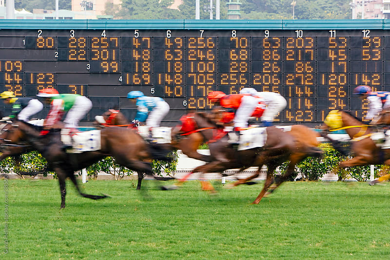 China, Hong Kong, Horses race past large scoreboard during a race at Happy Valley racecourse by Gavin Hellier for Stocksy United