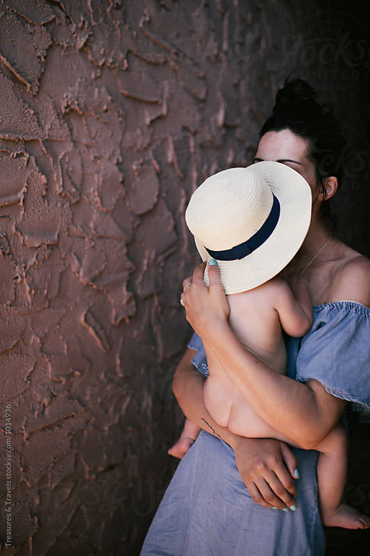 Mother holding naked baby on her hip by Treasures & Travels for Stocksy United