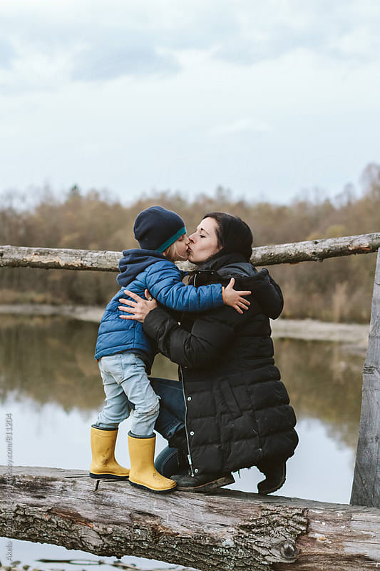 mother and son kissing on a wooden bridge in autumnal landscape by Leander Nardin for Stocksy United