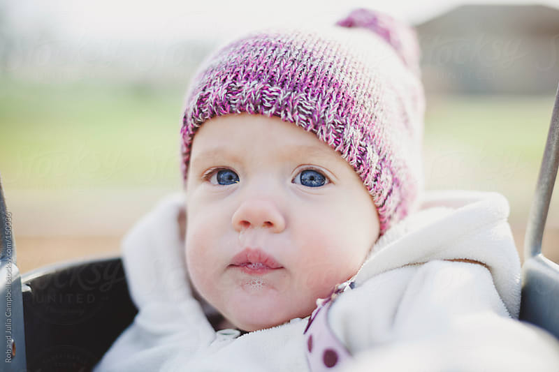Cute, serious baby outside in winter with knitted hat  by Rob and Julia Campbell for Stocksy United