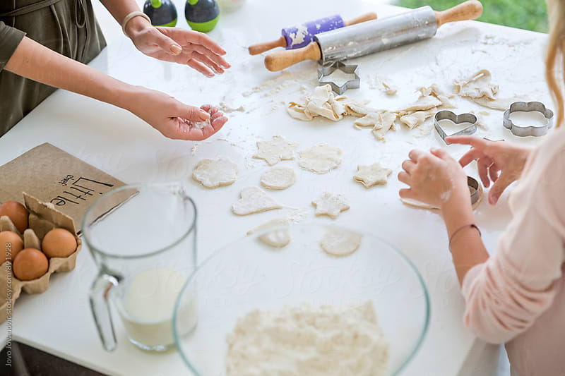 Mother and daughter making cookies together by Jovo Jovanovic for Stocksy United