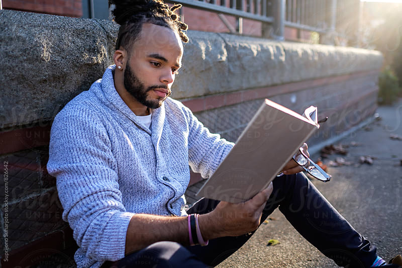 Male African American college student reading and studying on campus by Suprijono Suharjoto for Stocksy United