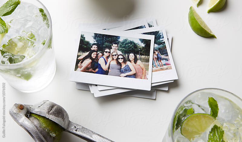 Stack of polaroid shots on table with mojito drinks by Guille Faingold for Stocksy United