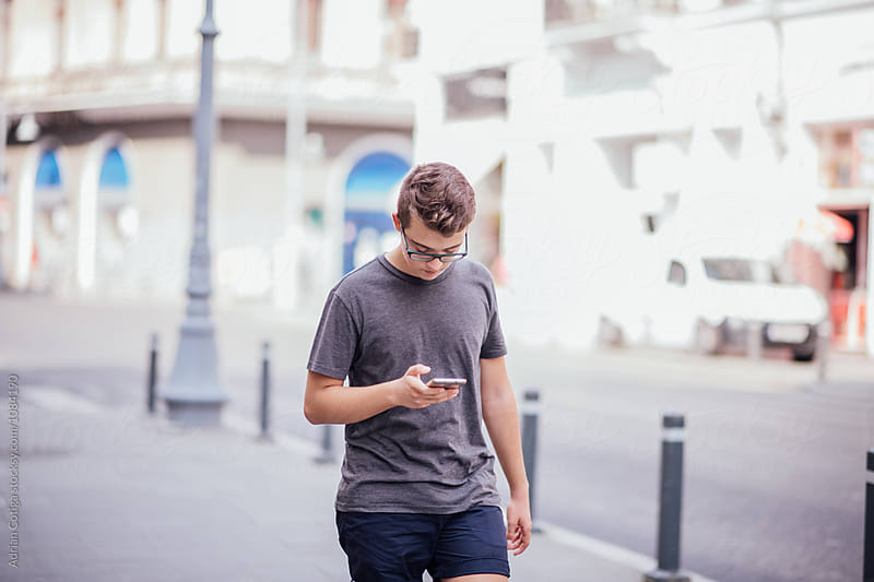 Teenager playing location-based augmented reality game on his smartphone in the city  by Adrian Cotiga for Stocksy United