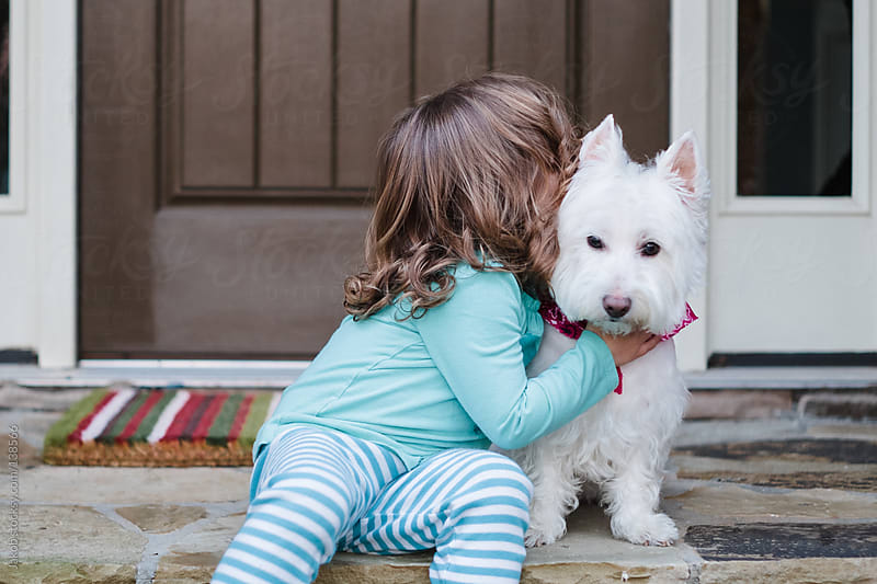 A toddler and her dog sitting on the steps in front of their home by Jakob for Stocksy United
