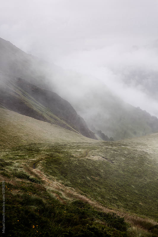Misty mountain landscape with path by Miquel Llonch for Stocksy United