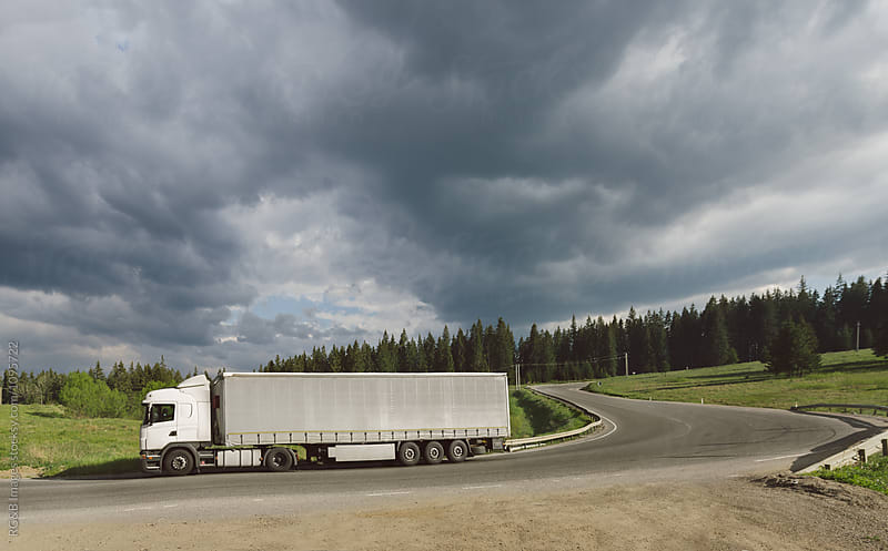 Cargo truck driving on a road though the countryside by RG&B Images for Stocksy United