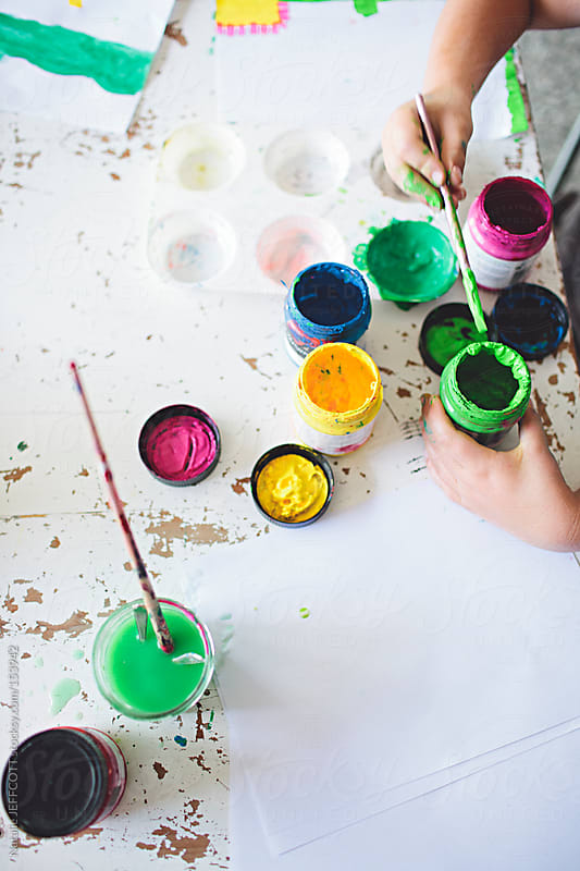 A young child mixing colourful pots of acrylic paint by Natalie JEFFCOTT for Stocksy United