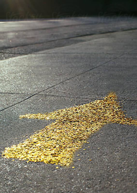Gold sequin arrow pointing forward on the sidewalk by Carolyn Lagattuta for Stocksy United