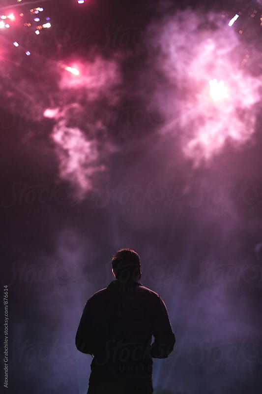 Man Looking At Fireworks by Alexander Grabchilev for Stocksy United