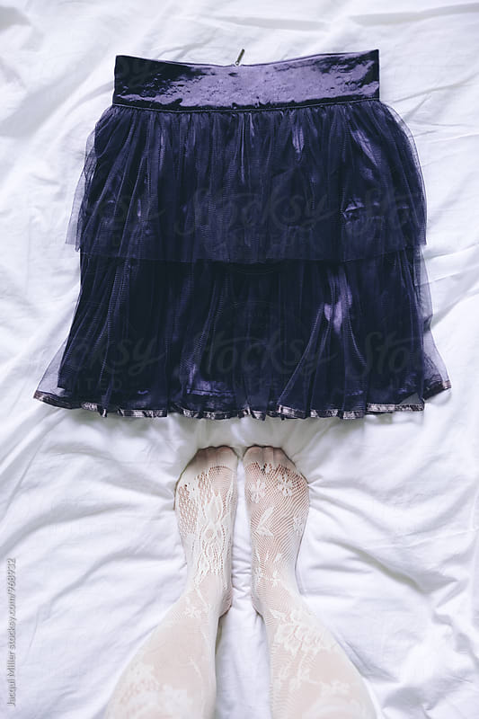 Looking down on woman's feet standing next to purple tulle skirt  by Jacqui Miller for Stocksy United