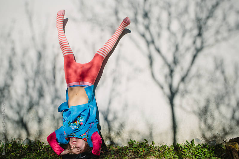 a girl wearing a dress and tights does a headstand against a wall  by Rebecca Zeller for Stocksy United