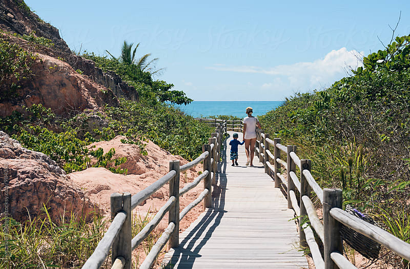 Mother and son walking down a wooden trail to a beach in Bahia, Brazil by Emmanuel Hidalgo for Stocksy United