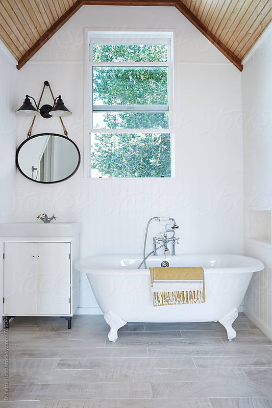 Clawfoot bathtub in cottage bathroom by Trinette Reed for Stocksy United