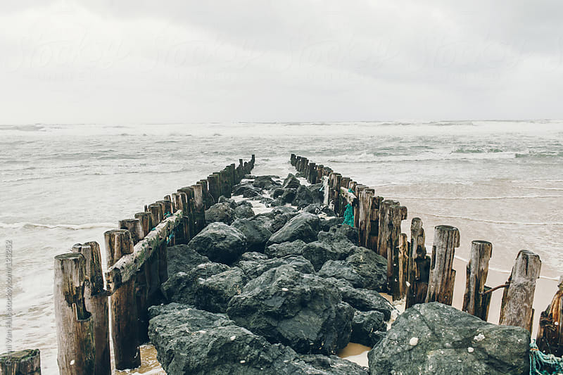 breakwater from rocks and wooden poles ending in the ocean water by Denni Van Huis for Stocksy United