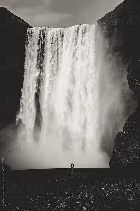 Standing at the bottom of a waterfall by Chris Zielecki for Stocksy United