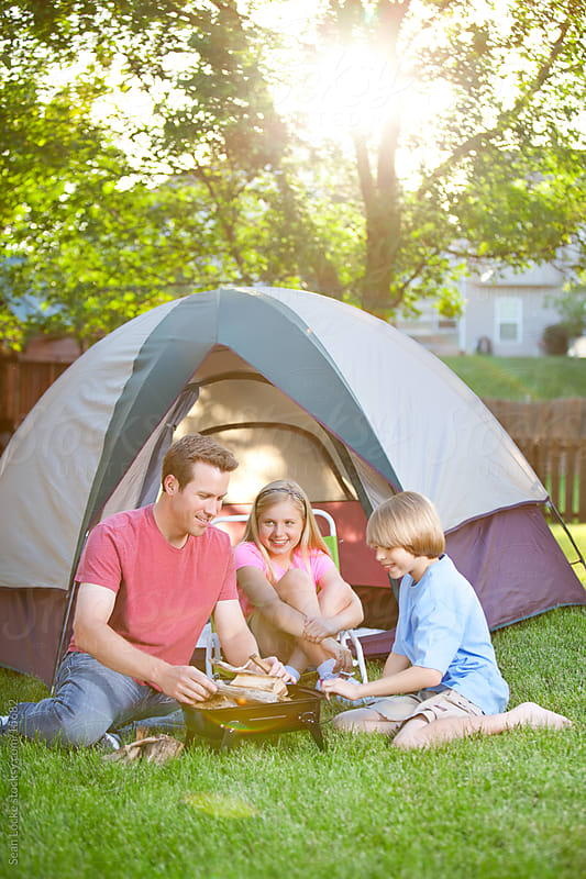 Camping: Family Starting Up Campfire to Cook by Sean Locke for Stocksy United