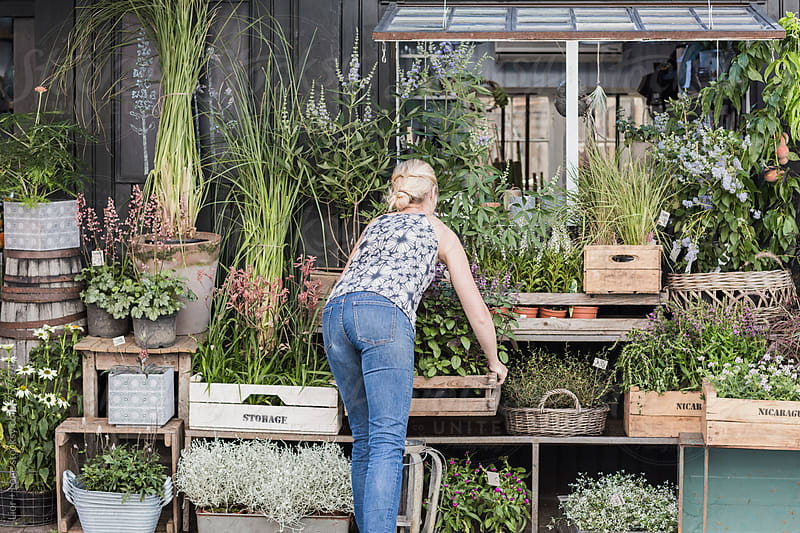 Woman arranging plants infant of a flower shop by Lior + Lone for Stocksy United